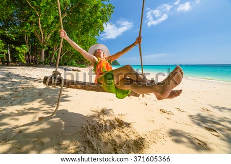 Happy and attractive woman with colorful sarongs and white wide-brimmed hat swinging on tropical white beach of Koh Rok Islands, Ko Lanta, Thailand paradise for snorkelers and divers. - stock photo