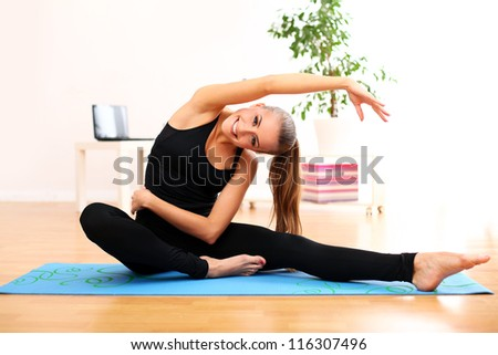 Happy and beautiful woman do yoga exercises at home on blue mat - stock photo