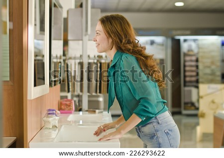 happy and beauty woman looking mirror at bath and plumbing store - stock photo
