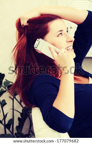 Happy and cheerful young woman sitting and talking by the phone. During phone conversation girl is holding her hair and handset and laughing. - stock photo