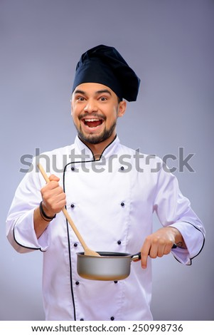 Happy and confident cook. Portrait of handsome cook holding a small pan and wooden spoon while standing over grey background with copy space