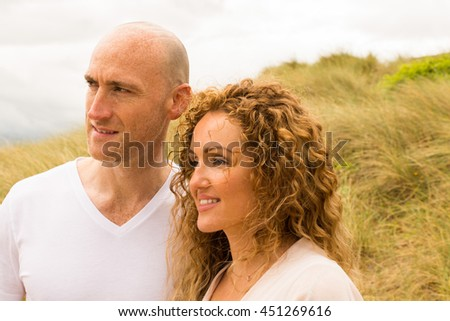 Happy and content couple enjoying a serene moment on beach in sand dunes