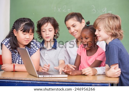 Happy and curious multiracial elementary students learning to use computer with teacher. - stock photo