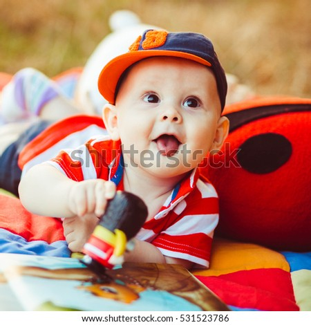 happy and cute little baby playing on colorful carpet outdoors