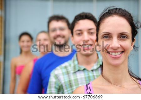 happy and diverse group of casual real people, mid adult woman in front - stock photo