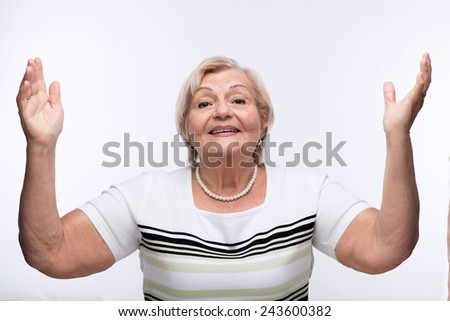 Happy and excited senior woman. Closeup portrait of smiling elderly woman raising her hands while standing against white background - stock photo