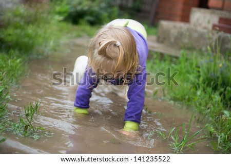 Happy and funny baby girl playing in puddles