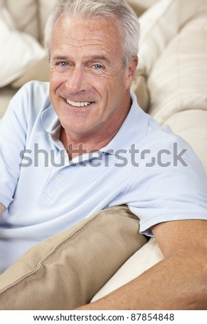 Happy and healthy senior man sitting on a sofa at home smiling and happy