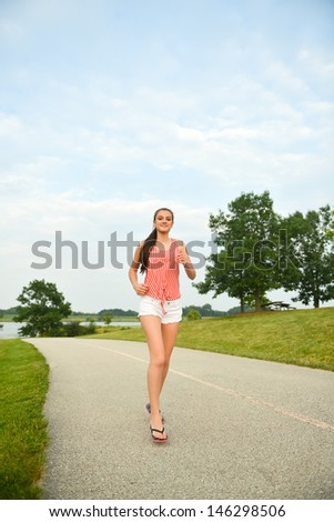 Happy and healthy woman walking/running in the park - stock photo