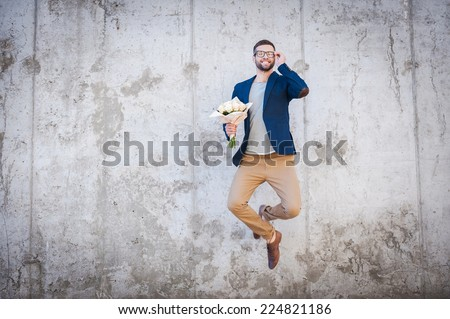Happy and in love. Happy young man in smart jacket holding bouquet of flowers and jumping in front of the concrete wall - stock photo