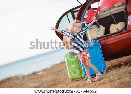 happy and joyful child in car and suitcases background. vacation and car trip concept. freedom and wind. girl traveler