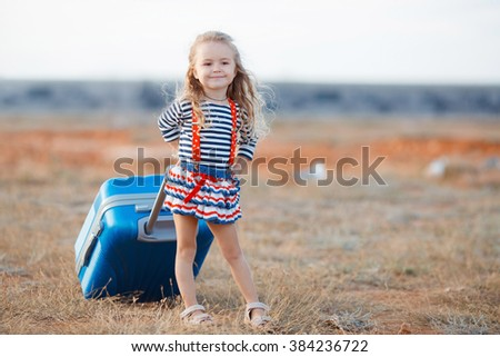 happy and joyful child in car and suitcases background. vacation and car trip concept. freedom and wind. girl traveler. holidays, voyage, sea and beach on background. summer time - stock photo