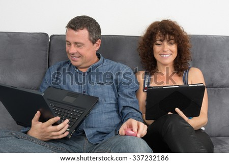 Happy and lovely couple on sofa at home looking at the tablet together