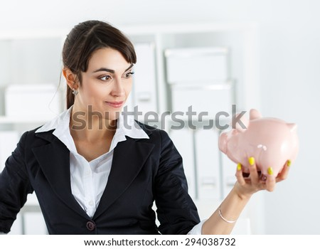 Happy and mysterious beautiful woman holding funny piggybank in hand, making face to it, planning something. Budgeting expenses, making savings and effective investment concept. Future needs deposit