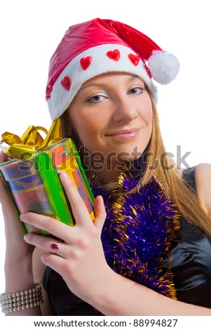 happy and positive looking caucasian blond girl with christmas gift and wearing xmas cap smiling over white