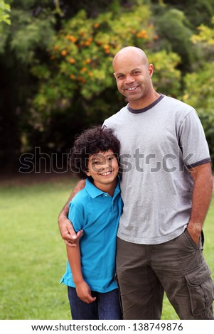 Happy and relaxed mixed race father and son family portrait in the garden with trees behind - copy space to left
