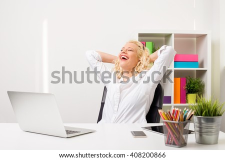Happy and relaxed woman at the office leaned back in her chair
