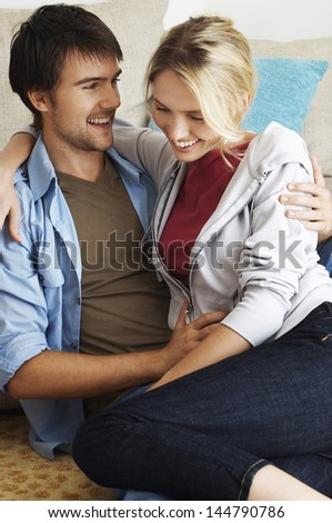 Happy and romantic young couple sitting in front of a couch