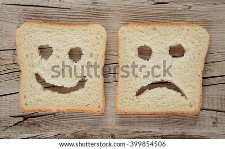 Happy and sad toast on a wooden board - stock photo