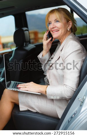 Happy and smile old senior business woman 60-65 years with white teeth, talking by mobile cell phone in the back of a car and holding her Laptop Computer pc in lap