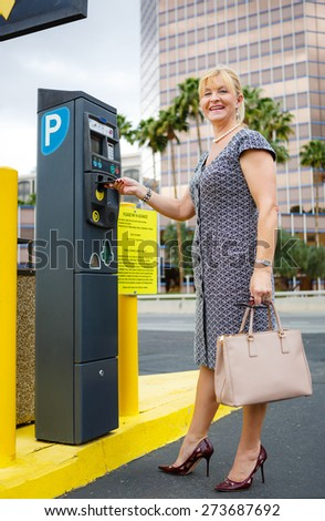 Happy and smile senior aged business woman 55-65 years with a lovely charming smile paying for parking in the street. Positive human emotion, facial expression - stock photo