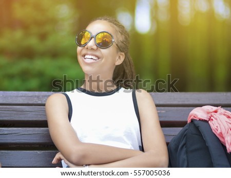 Happy and Smiling African American Teenage Girl With Long Dreadlocks Posing in Park Outdoors in Sunglasses. Horizontal Image Composition
