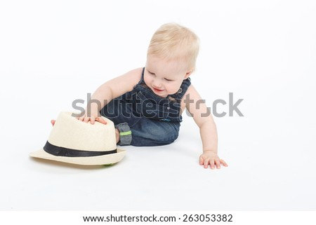 happy and smiling baby boy sitting on the floor with adult white hat - stock photo