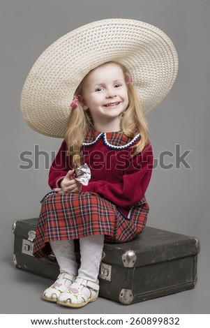 Happy And Smiling Caucasian Child Posing in Big Round Sombrero Hat and Sitting on Outdated Suitcase. Eating Chocolate Sweet. Against Gray Background. Vertical Image - stock photo
