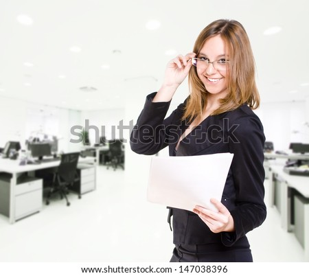 Happy and smiling secretary in the office with paper