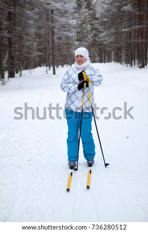Happy and smiling young woman skiing alone in winter forest