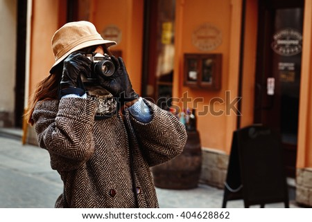happy and stylish hipster woman taking photo with film photo camera on background of old building in european city - stock photo