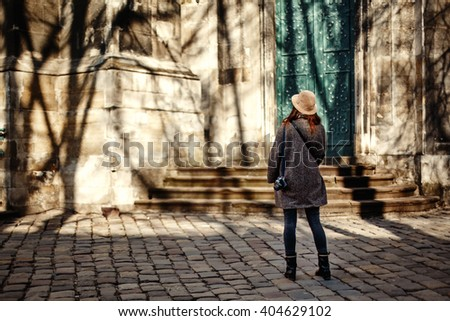 happy and stylish pretty hipster woman holding film photo camera on background of old building  in european city - stock photo