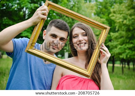 Happy and young  couple outdoors with photo frame - stock photo