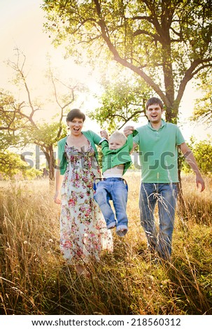 Happy and young family relaxing together in summer nature - stock photo