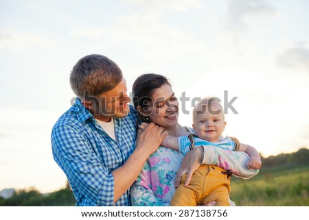 happy and young family with baby spending time in the park (lens focus on mother) - stock photo