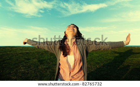 Happy and young female relaxing in the sun - stock photo
