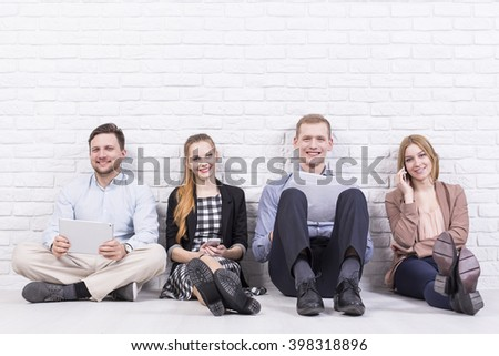 Happy and young men and woman sitting on floor in light interior, brick wall in the background - stock photo