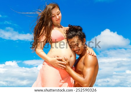Happy and young pregnant couple having fun on a tropical beach. Summer vacation. New life concept. Future mother and father.