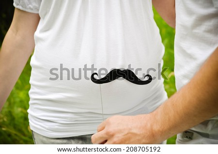 Happy and young pregnant couple outdoors with mustache near belly - stock photo