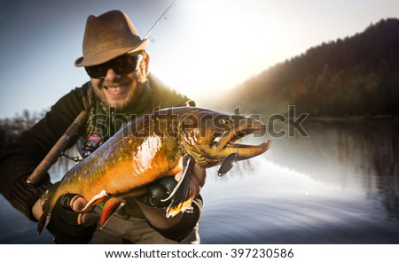 Happy angler with trout fishing trophy  - stock photo
