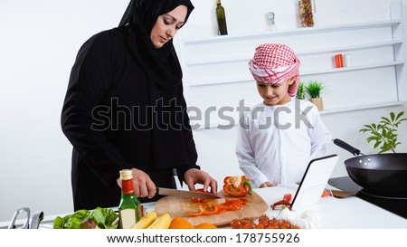 Happy Arabic child in the kitchen with his mother - stock photo