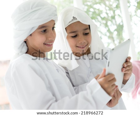 Happy Arabic family members with tablet - stock photo
