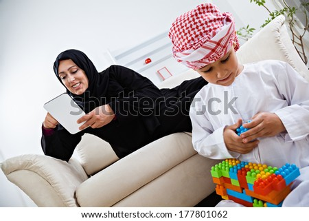 Happy Arabic mother and son together at home. - stock photo