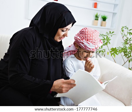 Happy Arabic mother and son together sitting on the couch and reading a book.