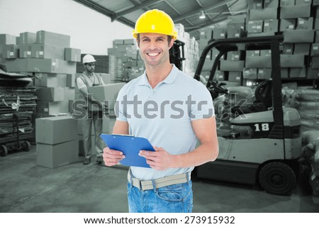 Happy architect holding clip board against warehouse worker loading up pallet - stock photo