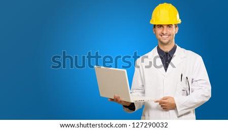 Happy Architect Holding Laptop On Blue Background - stock photo