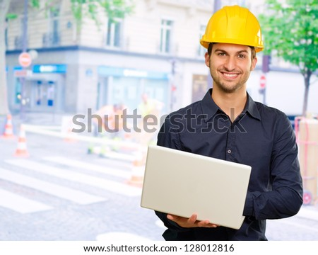 Happy Architect Holding Laptop, Outdoors - stock photo