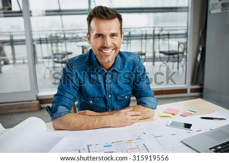 Happy architect working at office, looking at camera - stock photo