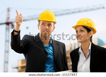 Happy architects wearing protective helmet working and talking on construction site.