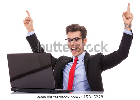 Happy arm rising winning business man at his desk working on laptop